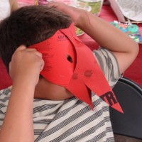"Student with his ""Raven"" cut & folded paper mask"